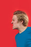 Agressive young man. Man looking agressive and ready to fight on red background Stock Photography