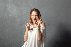 Agressive young woman posing with hands Stock Image