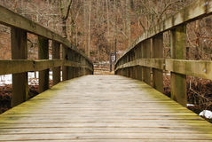 Agrestic Link. This is a shot of a wooded bridge walkway over a river. A little bit of the river can be seen on either side of the bridge. Woods can be seen on Royalty Free Stock Photo