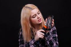 Agresywna dziewczyna, cięcia ekran łamani smartphones używać budowa nóż Czarny tło Fotografia Stock