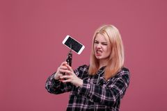 Agresywna dziewczyna, przerwy smartphone z kahatem Na różowym tle Obrazy Stock