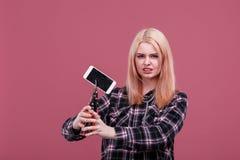 Agresywna dziewczyna ze złością gniósł nowożytnego telefon komórkowego z czopującym ekranem Różowy tło Zdjęcie Stock