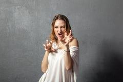 Agresywna młoda kobieta pozuje z rękami Obraz Stock