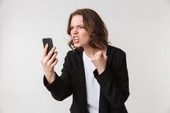 Agresywna młodej kobiety pozycja opowiada telefonem Fotografia Stock