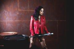 Agresywna punkowa kobieta z nietoperzem w czerwonej skórzanej kurtce, Fotografia Stock