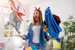 Agresywna sfrustowana kobieta rzuca pralnię w powietrzu Obraz Stock