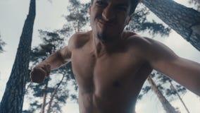 Agresywny bez koszuli mężczyzna brutalnie bije łgarski przeciwnik plenerowego przy lasem Puka za długach zbiory