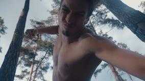 Agresywny bez koszuli m??czyzna brutalnie bije ?garski przeciwnik plenerowego przy lasem Puka za d?ugach zbiory