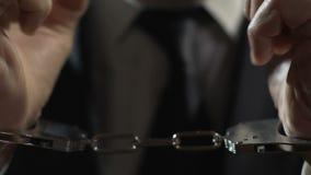 Agresywny biznesmen aresztujący w kajdankach, samiec karząca dla przestępstwa, przestępstwo zdjęcie wideo