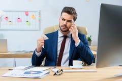 agresywny biznesmen opowiada smartphone i miie prześcieradło Fotografia Stock