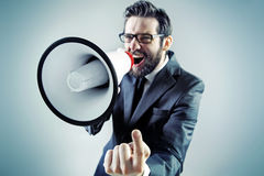 Agresywny biznesmen wrzeszczy nad megafonem fotografia royalty free