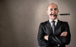 Agresywny biznesmen z nożem między zębami Fotografia Stock