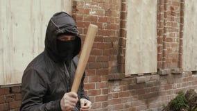 Agresywny chuligan w maski i kapiszonu ganging z kijem bejsbolowym, żurawia strzał zbiory