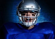 Agresywny futbolu amerykańskiego gracz krzyczy przeciw błękit ściany tłu w hełmie Zdjęcie Stock