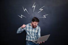 Agresywny mężczyzna iść łamać laptop nad chalkboard tłem Zdjęcie Royalty Free