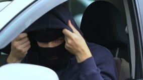 Agresywny mężczyzna jest ubranym twarzy maskę przed rabunkiem, polowanie dla bogactwa, bandytyzm zdjęcie wideo