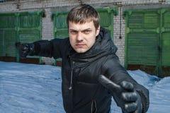 Gniewny mężczyzna uderza pięścią w ulicznej walce. Zdjęcie Royalty Free