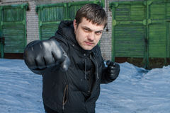 Gniewny mężczyzna uderza pięścią w ulicznej walce. Obraz Royalty Free