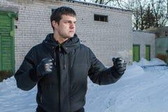 Gniewny mężczyzna uderza pięścią w ulicznej walce. Obrazy Royalty Free