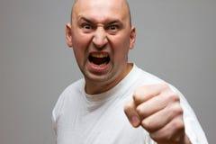 Agresywny mężczyzna, trzyma jego pięść up na czarnym tle Obrazy Stock