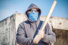 Agresywny mężczyzna z kijem bejsbolowym na budynku tle Obraz Stock