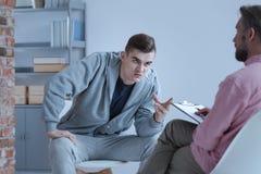 Agresywny młody człowiek i psychoterapeuta podczas terapii dla rebe Zdjęcie Royalty Free