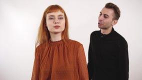 Agresywny młody człowiek wrzeszczy przy piękną kobietą z czerwonym włosy Żeński liczenie z palcami liczba trzy zbiory wideo