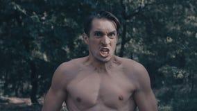 Agresywny m??czyzna w?ciekle krzyczy w lesie z nag? p??postaci? zbiory