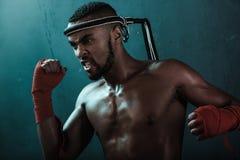 Agresywny młody Muay tajlandzki bokser trenuje tajlandzkiego boks Zdjęcie Stock