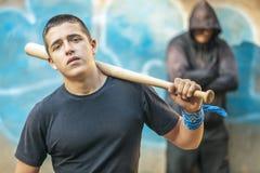 Agresywny nastolatek z kijem bejsbolowym na budynku tle Zdjęcia Royalty Free