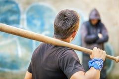 Agresywny nastolatek z kijem bejsbolowym przeciw mężczyzna przy plenerowym Zdjęcia Stock