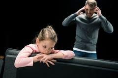 Agresywny ojciec stoi blisko wzburzonego córki obsiadania na leżance Zdjęcie Royalty Free