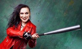 Agresywny punkowy kobieta strajk someone z nietoperzem w czerwonej skórzanej kurtce, Obrazy Stock