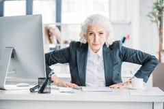 Agresywny starszy bizneswomanu obsiadanie przy miejscem pracy i patrzeć kamerę Fotografia Royalty Free