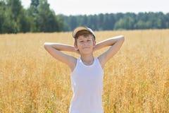 Agricoltore adolescente che sta fra il campo dell'avena Fotografia Stock Libera da Diritti