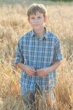 Agricoltore adolescente che sta fra il campo di orzo Fotografia Stock
