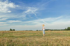 Agricoltore adolescente che sta sul campo raccolto Immagine Stock