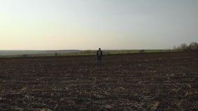 Agricoltore adulto che esamina campo arato, preparante terra per seminare Concetto stagionale degli impianti agricoli stock footage