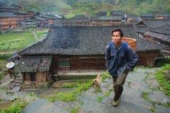 Agricoltore agricolo dell'uomo asiatico del paesano con un canestro di vimini sulle sue sedere Immagine Stock