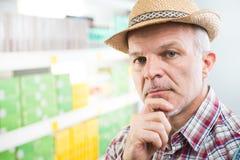 Agricoltore al supermercato con la mano sul mento Fotografia Stock
