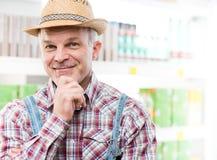 Agricoltore al supermercato con la mano sul mento Immagini Stock