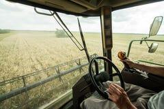 Agricoltore al volante della mietitrice di ombine del  di Ñ su un giacimento di grano Fotografia Stock