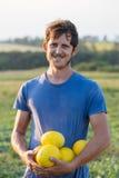 Agricoltore allegro che tiene il raccolto fresco del melone sul campo all'azienda agricola organica di eco Fotografia Stock