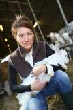 Agricoltore allegro che tiene una capra del bambino Fotografie Stock Libere da Diritti