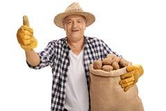 Agricoltore anziano che tiene un sacco della tela da imballaggio e che dà un pollice su Fotografie Stock