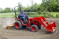 Agricoltore anziano Tilling His Garden con un trattore compatto 4x4 Immagine Stock
