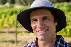 Agricoltore bello che sorride nel campo un giorno soleggiato Fotografia Stock