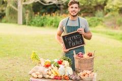 Agricoltore bello che sta alla sua stalla e che tiene lavagna Fotografie Stock