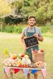 Agricoltore bello che sta alla sua stalla e che tiene lavagna Fotografia Stock