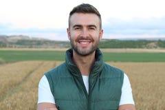 Agricoltore bello felice che gesturing nel campo pronto a raccogliere dare un pollice su Fotografia Stock